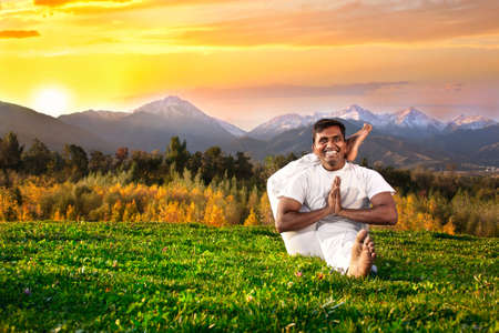 eka: Yoga eka pada shirasana foot behind the head pose by happy Indian Man in white cloth in the morning at mountain and sunset sky background
