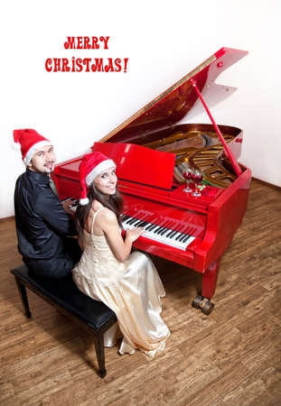 carol: Christmas party with Man and woman in Christmas hats playing the piano and smiling with wine glasses and red rose on the red grand piano. Free space for text