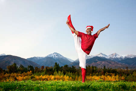 Christmas yoga utthita Hasta Padangustasana pose by happy Indian man in white trousers, red socks and Christmas hat at mountain background. Free space for text photo
