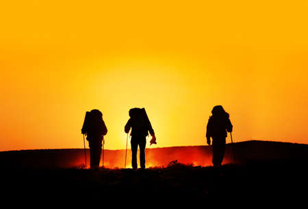 guy with walking stick: Three tourist silhouettes walking on the hills with track sticks and backpacks at sunset orange background. Free space for text, good template for web design