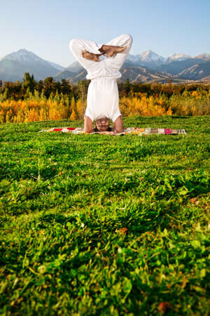 shirshasana: Yoga urdhva padmasana head standing with lotus pose by happy Indian Man in white cloth in the morning at mountain background