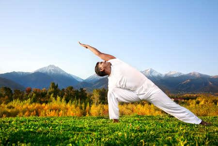 протяжение: Йога Утхита parsvakonasana треугольника представляют по счастливой индийской Человек в белой тканью утром в горном фоне