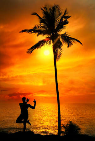 indian ocean: Yoga lord krishna pose by Man in silhouette with palm tree nearby outdoors at ocean and sunset background. Vagator beach, Goa, India