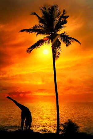 Yoga Urdhva Prasarita Eka Padasana pose by Man in silhouette with palm tree nearby outdoors at ocean and sunset background. Vagator beach, Goa, India photo