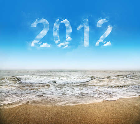 2012 new year message in the blue sky with clouds. Beach and ocean under it. Free space for text photo