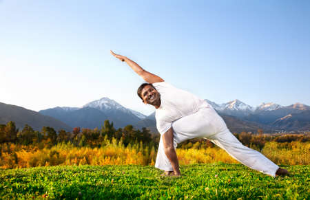 parsvakonasana: Yoga parivrita parsvakonasana triangle pose by happy Indian Man in white cloth in the morning at mountain background