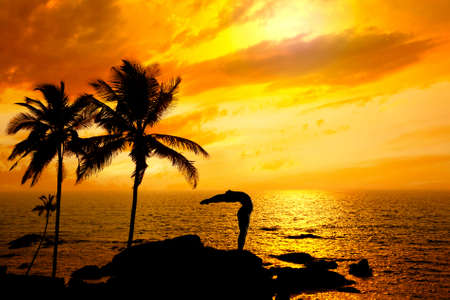 Yoga Hasta Uttanasana raised arms pose from surya namaskar by Man in silhouette with palm tree nearby outdoors at ocean and sunset background. Vagator beach, Goa, India photo