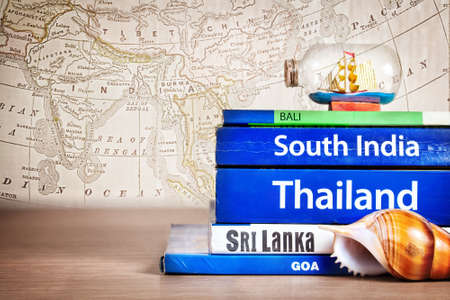Guide books on the table with Seashell and ship in the bottle on its at old map background. Books with titles: South India, Bali, Sri Lanka, Goa, Thailand