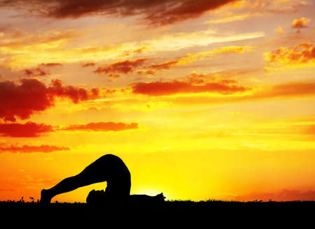 Yoga inverse pose by Man in silhouette with orange sunset sky background. photo