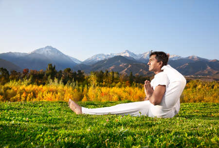 indian yoga: Yoga meditation foot behind the head pose by concentrate Indian Man in white cloth in the morning at mountain and blue sky background.