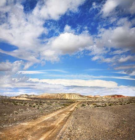Camino a las montañas a través del desierto en el cielo con nubes