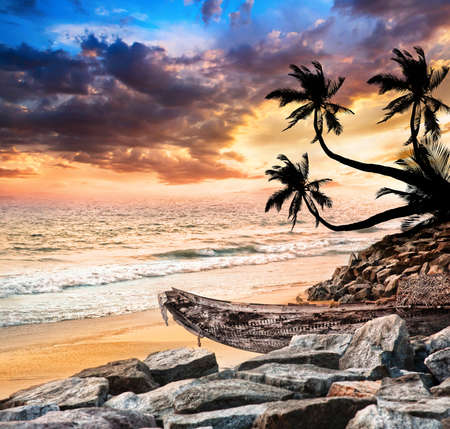 kerala: Fishing boat on the beach near the ocean at dramatic sunset sky and palm trees in silhouette nearby   Stock Photo