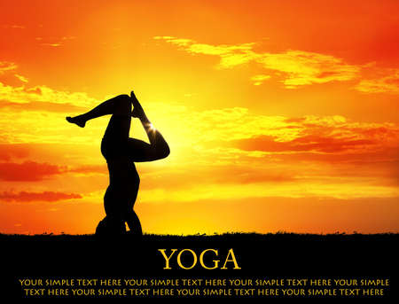 Yoga shirshasana head standing inverse pose with bending legs by Man in silhouette with orange sunset sky background. Free space for text and can be used for web-site photo