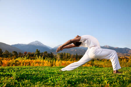 yoga class: Yoga virabhadrasana I warrior pose by Indian Man in white cloth in the morning at mountain background