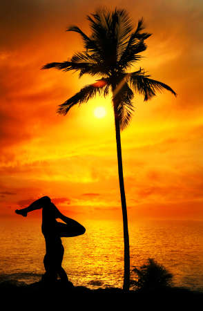 Yoga shirshasana head standing pose by Man in silhouette with palm tree nearby outdoors at ocean and sunset background. Vagator beach, Goa, India photo