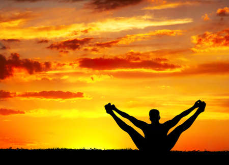 Yoga merudandasana balancing bear pose by Man in silhouette with orange sunset sky background. Free space for text photo