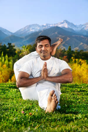 shirshasana: Yoga meditation eka pada shirshasana foot behind the head pose by concentrate Indian Man in white cloth in the morning at mountain and blue sky background. Free space for text