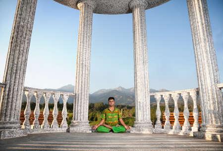 dhyana: Yoga padmasana loto da uomo indiano di panno verde nei pressi della colonna di pietra a sfondo montagna Archivio Fotografico