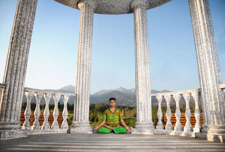 dhyana: Yoga padmasana lotus pose by Indian man in green cloth near stone column at mountain background Stock Photo
