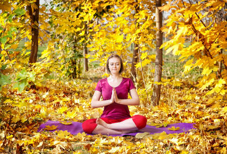 namaste: Yoga meditation pose by concentrate beautiful woman in red cloth and yellow leaves around in the autumn