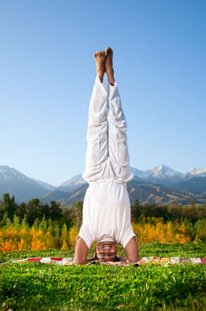 shirshasana: Yoga shirshasana head standing pose by happy Indian Man in white cloth in the morning at mountain background
