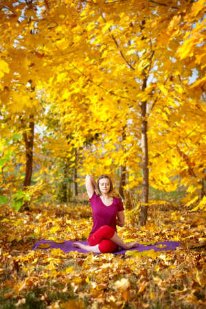 Yoga gomukhasana cow pose by concentrate beautiful woman in red cloth and yellow leaves around in the autumn photo