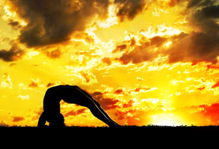 dwi: Yoga Dwi Pada Viparita Dandasana Upward Facing Two-Foot Staff Pose inverse pose by Man in silhouette with orange sunset sky background. Free space for text Stock Photo