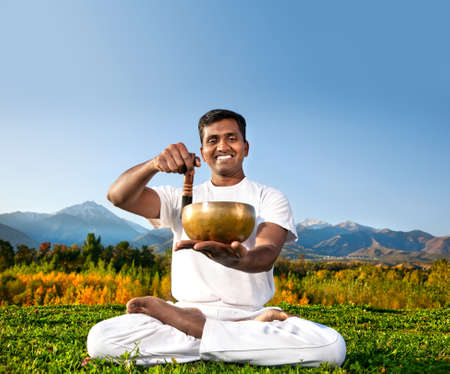 Yoga meditation practice with singing Tibetan bowl by happy Indian Man doing padmasana in white cloth in the morning at mountain background. Free space for text photo