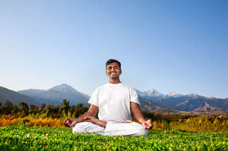 Yoga meditation in padmasana pose by happy Indian Man in white cloth in the morning at mountain background. Free space for text photo