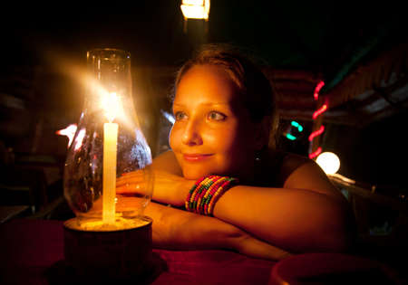 wristlet: Beautiful Woman looking at candle, smiling and waiting her dinner in restaurant  India, Kerala, Varkala  Stock Photo