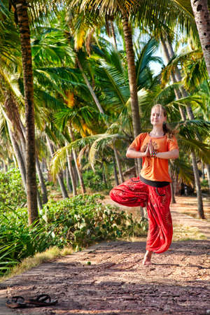 vriksasana: Yoga vrikshasana tree balancing pose by beautiful Caucasian woman in red Indian trousers with symbol om on the road with shoes off in palm tree forest in India, Kerala, Varkala Stock Photo