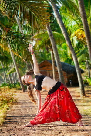 Yoga trikonasana triangle pose by beautiful Caucasian woman in red Indian trousers with symbol om on the road in palm tree forest with house at background in India, Kerala, Varkala Stock Photo