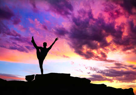 Yoga utthita Hasta Padangustasana balance pose by man silhouette with purple dramatic sunset sky background. Free space for text and can be used as template for web-site photo