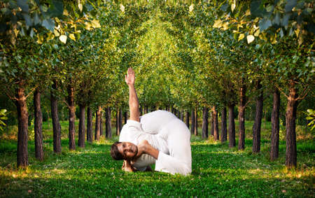 Yoga bal krishnasana difficult pose by Indian man in white cloth. Green trees around him