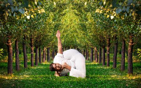 Yoga bal krishnasana pongono difficili da uomo indiano in panno bianco. Alberi verdi intorno a lui