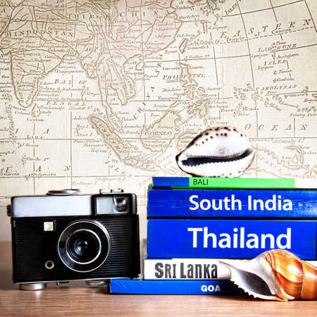 Retro photo camera near Guide books on the table with Seashell on its at old map background. Books with titles: South India, Bali, Sri Lanka, Goa, Thailand Imagens