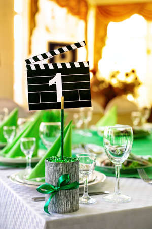 wedding table setting: Wedding table served in green colors in movie style with clapboard and number one on it