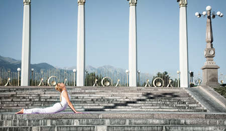 bhujangasana: Yoga bhujangasana cobra pose by Caucasian woman in white cloth, step of surya namaskar sun salutation Exercise. Woman laying in prone position on stone stairs. Columns, mountains at background Stock Photo