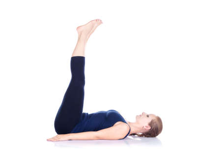 Yoga uttanpadasana double leg raise pose by beautiful Caucasian woman in blue Capri and top at white background. Free space for text