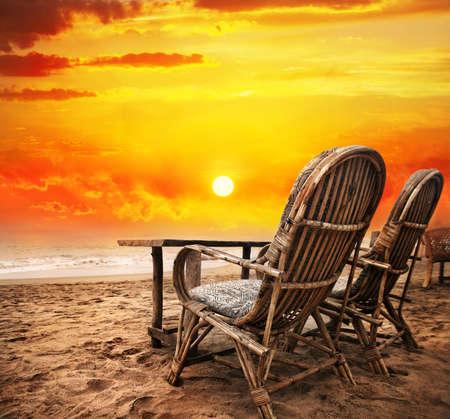 Zwei Stühle mit Blick auf den Sonnenuntergang orange Himmel und Meer in Goa, Indien