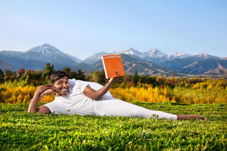 Indian Man in white cloth doing Yoga eka pada shirshasana foot behind the head pose and reading orange book at mountain and blue sky background. Free space for text on the book and sky photo