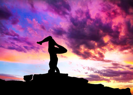 Yoga shirshasana head standing inverted pose by man silhouette with purple dramatic sunset sky background. Free space for text and can be used as template for web-site photo