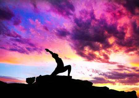 Yoga virabhadrasana I warrior pose by man silhouette with purple dramatic sunset sky background. Free space for text and can be used as template for web-site photo