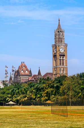 национальной достопримечательностью: Rajabai башня с часами в готическом стиле и зеленом поле крикету в Мумбаи, Махараштра, Индия Фото со стока