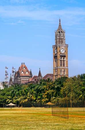 maharashtra: Rajabai clock tower in gothic style and green cricket field in Mumbai, Maharashtra, India Stock Photo