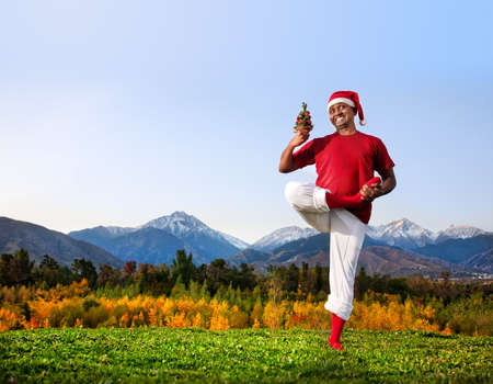 Christmas yoga vrikshasana tree pose by happy Indian man in white trousers, red socks and Christmas hat with Christmas tree at mountain background. Free space for text Stock Photo - 11270306
