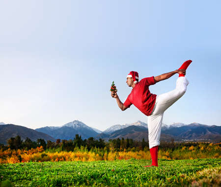 Christmas yoga natarajasana dancer pose by funny Indian man in white trousers, red socks and Christmas hat with looking at Christmas tree at mountain background. Free space for text photo