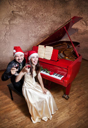 Christmas party with Man and woman in Christmas hats drinking wine and laughing near the red grand piano with red rose on it at grunge textured background. Free space for text  photo