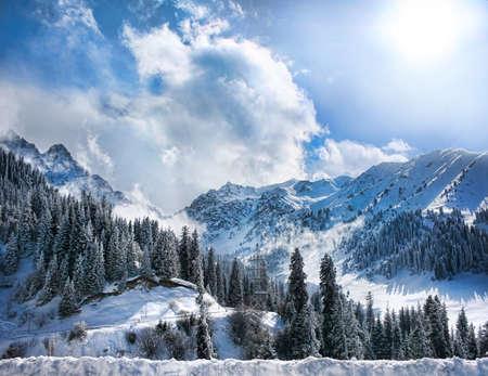Invierno Montañas valle nevado con niebla y sol en Chumbulak, Almaty, Kazajstán