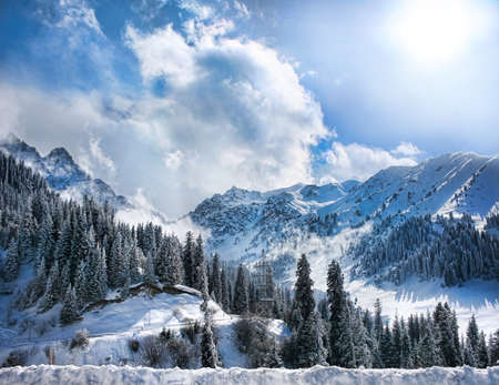 Winter Snowy Mountains valley with fog and sun in Chumbulak, Almaty, Kazakhstan Stock Photo